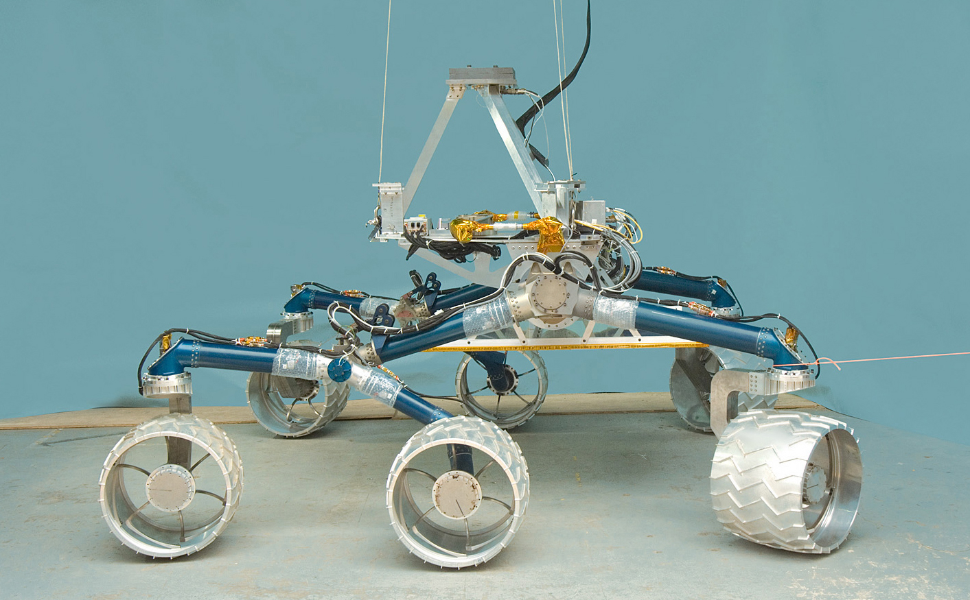 In this image, a large, six-wheeled rover sits on a concrete floor in a laboratory against a light-blue background.  The rover's 'legs,' or mobility system are a medium blue color and the large, cleated wheels are shiny silver.  On top of the mobility system is a silver-colored triangle that represents where the heart and brains of the rover will go when it is complete.