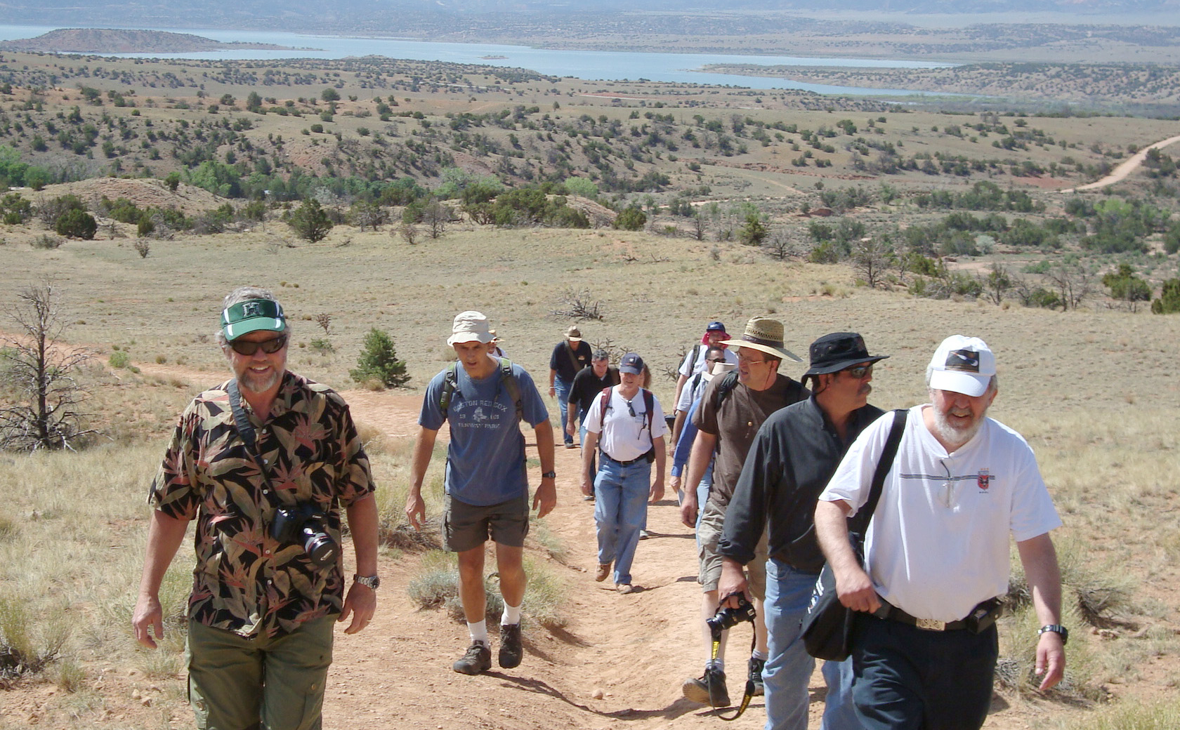 In this image, the Mars Science Laboratory Project Science Group, consisting of 11 men and 1 woman, are climbing up a dusty trail in New Mexico.  Wearing casual hiking clothes and hats, they are climbing towards the photographer of this image.  Behind them in the distance is a lake and mountains.