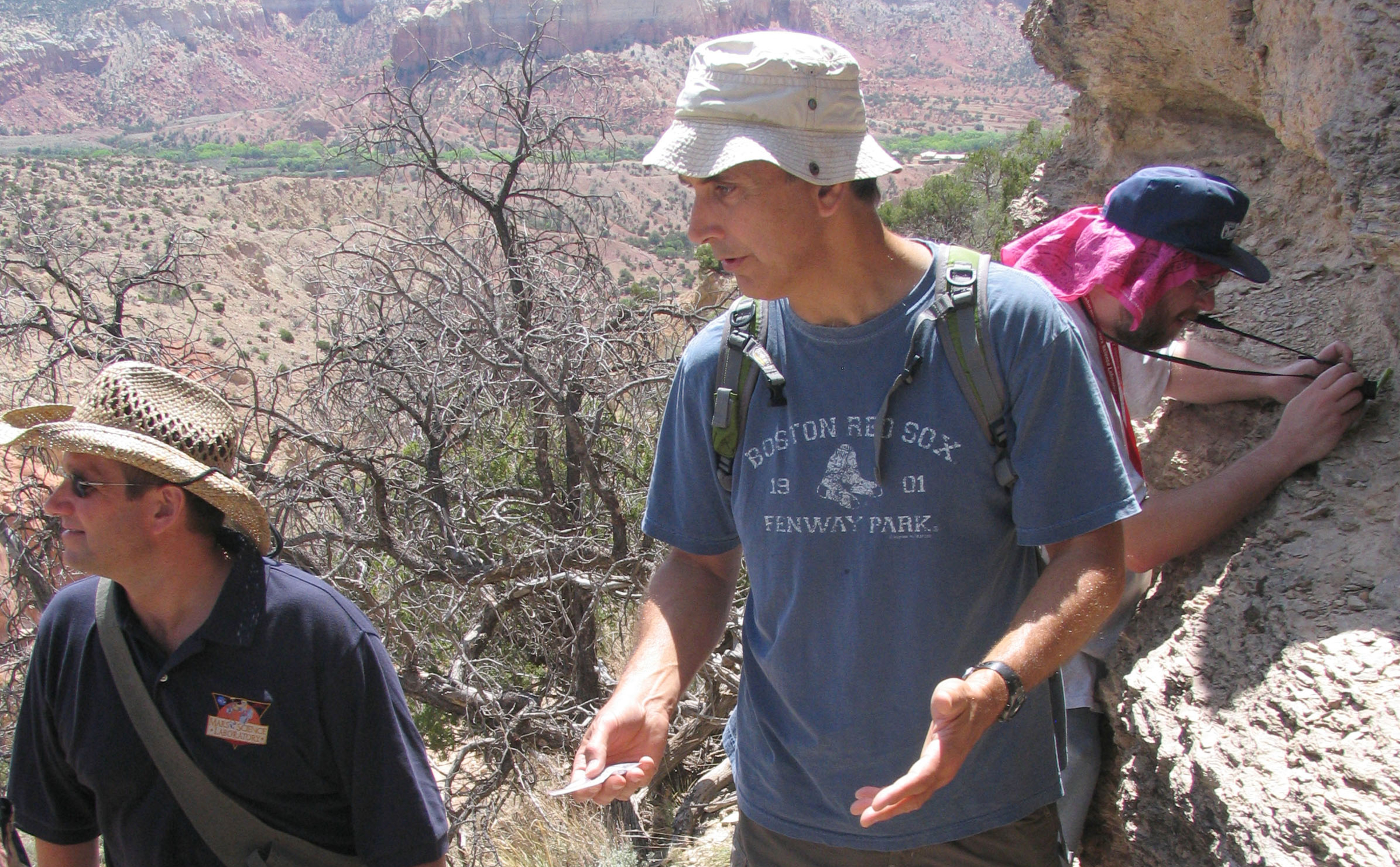 John Grotzinger is standing at the face of a cliff and in discussion with two other team members.  The cliff, which is beige and gray in color, has many layers in the rocks.  Ken Edgett, wearing a baseball hat with a red handkerchief hanging out the back to protect his neck from the sun, is taking close-up pictures of the cliff with a small black camera.