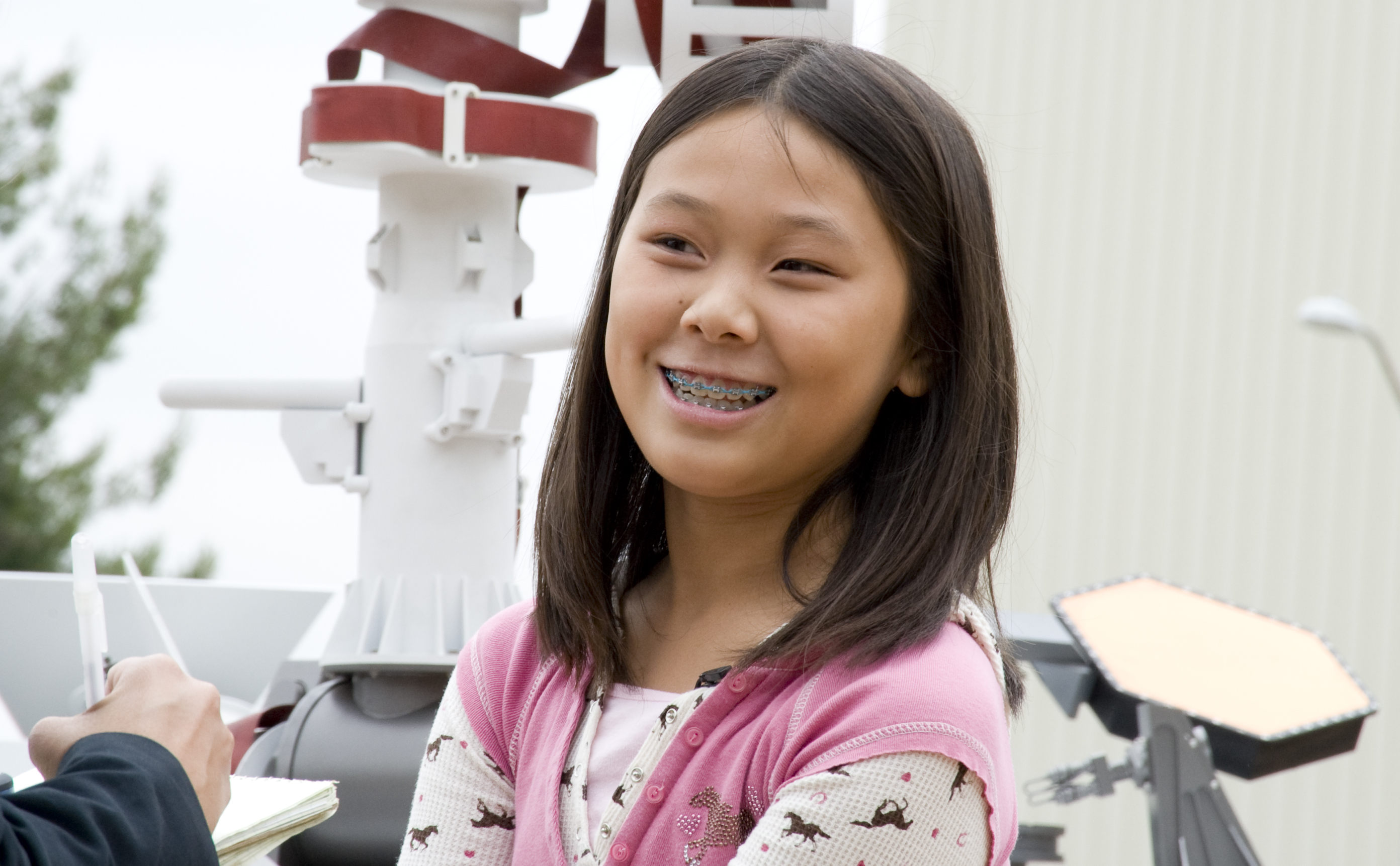 Clara Ma poses with a model of Curiosity.