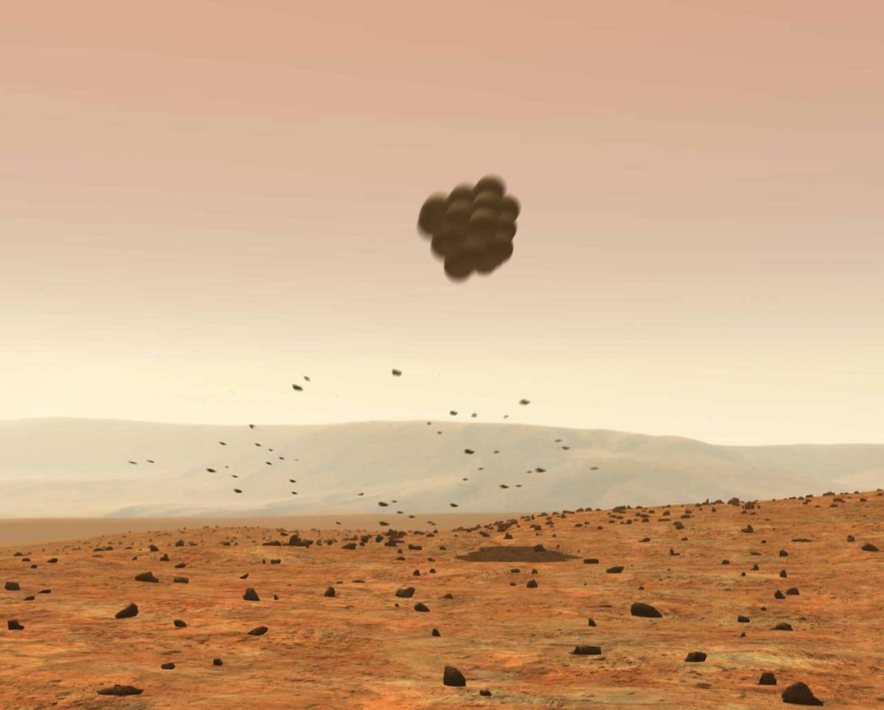 Protected by large airbags, the lander falls away from the parachute, landing safely on Mars.