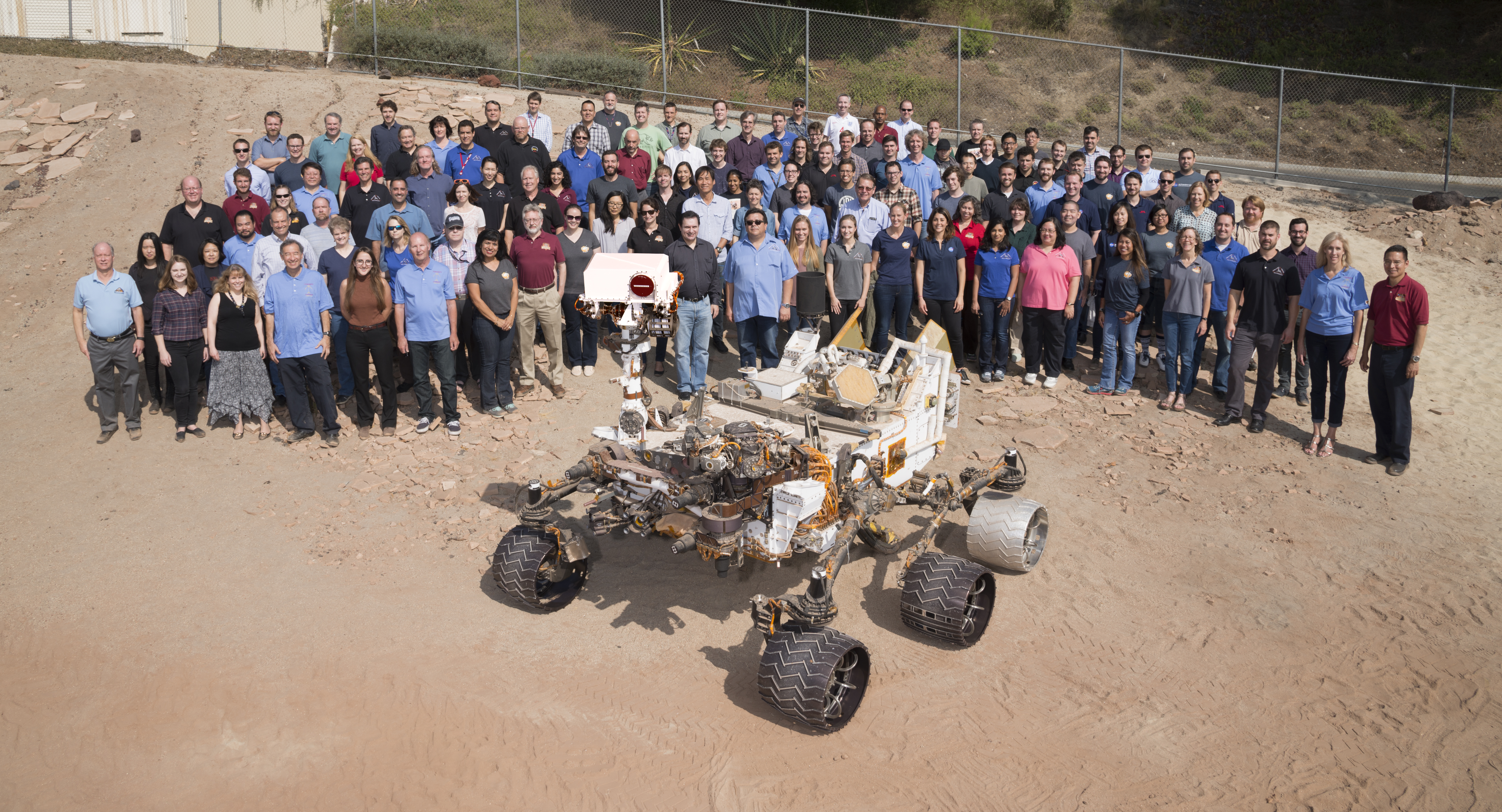 "Many members of NASA's Mars Science Laboratory Project, which operates the Curiosity rover on Mars, gathered for this 2016 team photo with a test rover in the ""Mars Yard"" at NASA's Jet Propulsion Laboratory, Pasadena, California."