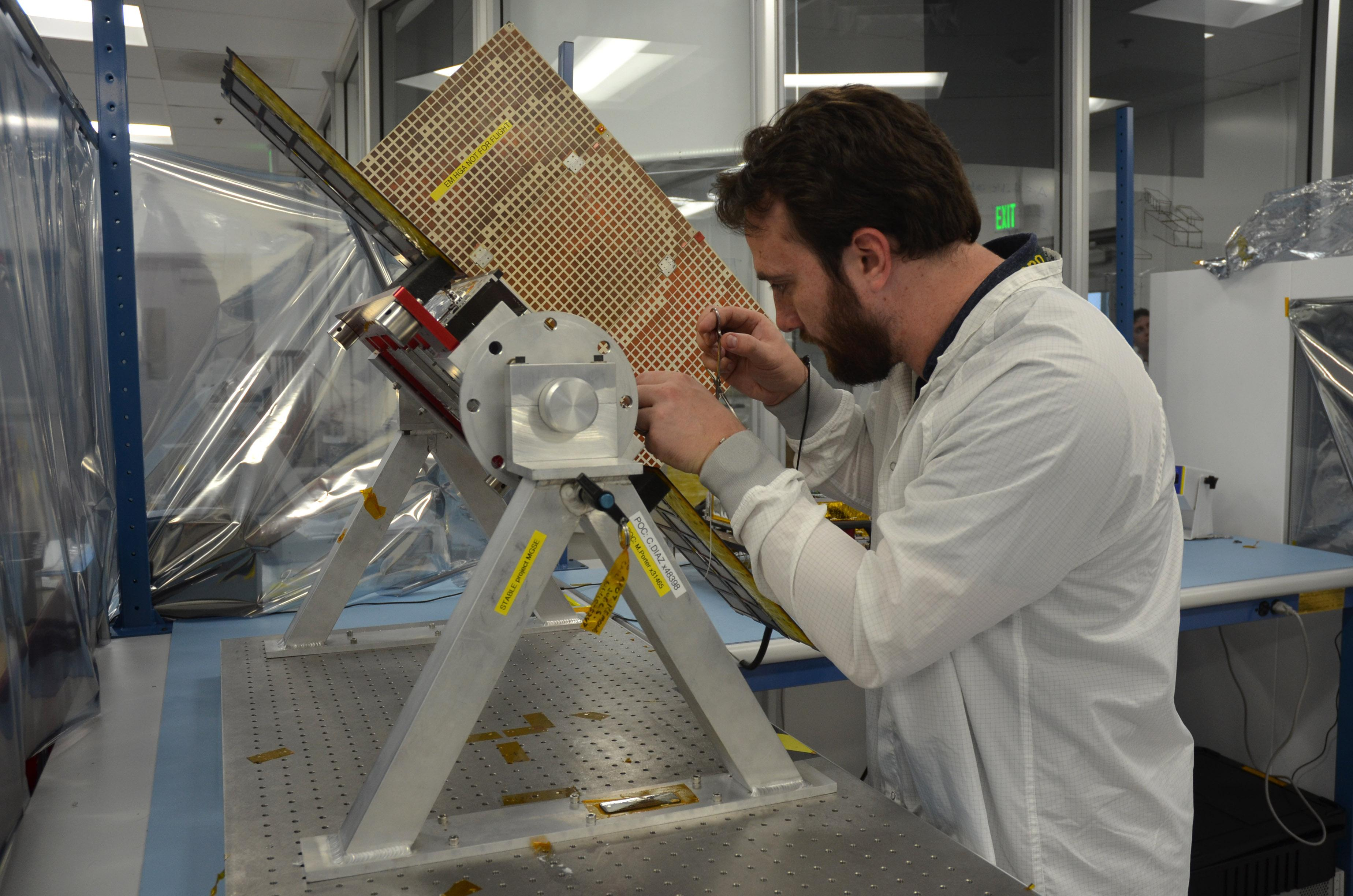 Joel Steinkraus, lead mechanical engineer for the MarCO (Mars Cube One) CubeSat spacecraft, adjusts a model of one of the two spacecraft.