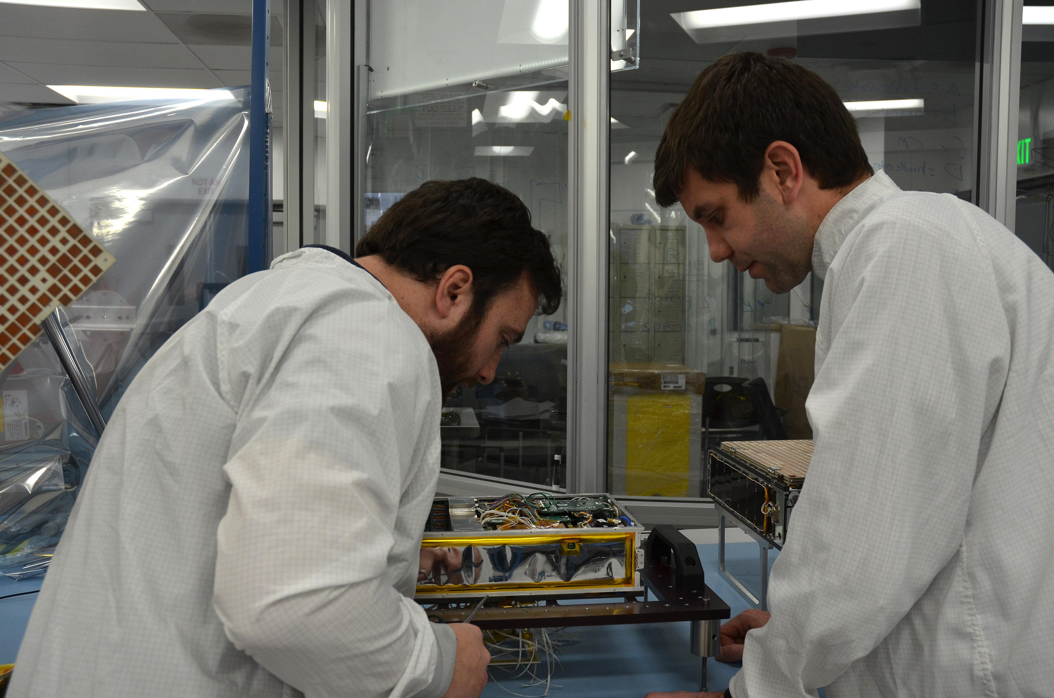 Engineers for NASA's MarCO (Mars Cube One) technology demonstration inspect one of the two MarCO CubeSats. Joel Steinkraus, MarCO lead mechanical engineer, left, and Andy Klesh, MarCO chief engineer, are on the team at NASA's Jet Propulsion Laboratory, Pasadena, California, preparing twin MarCO CubeSats.