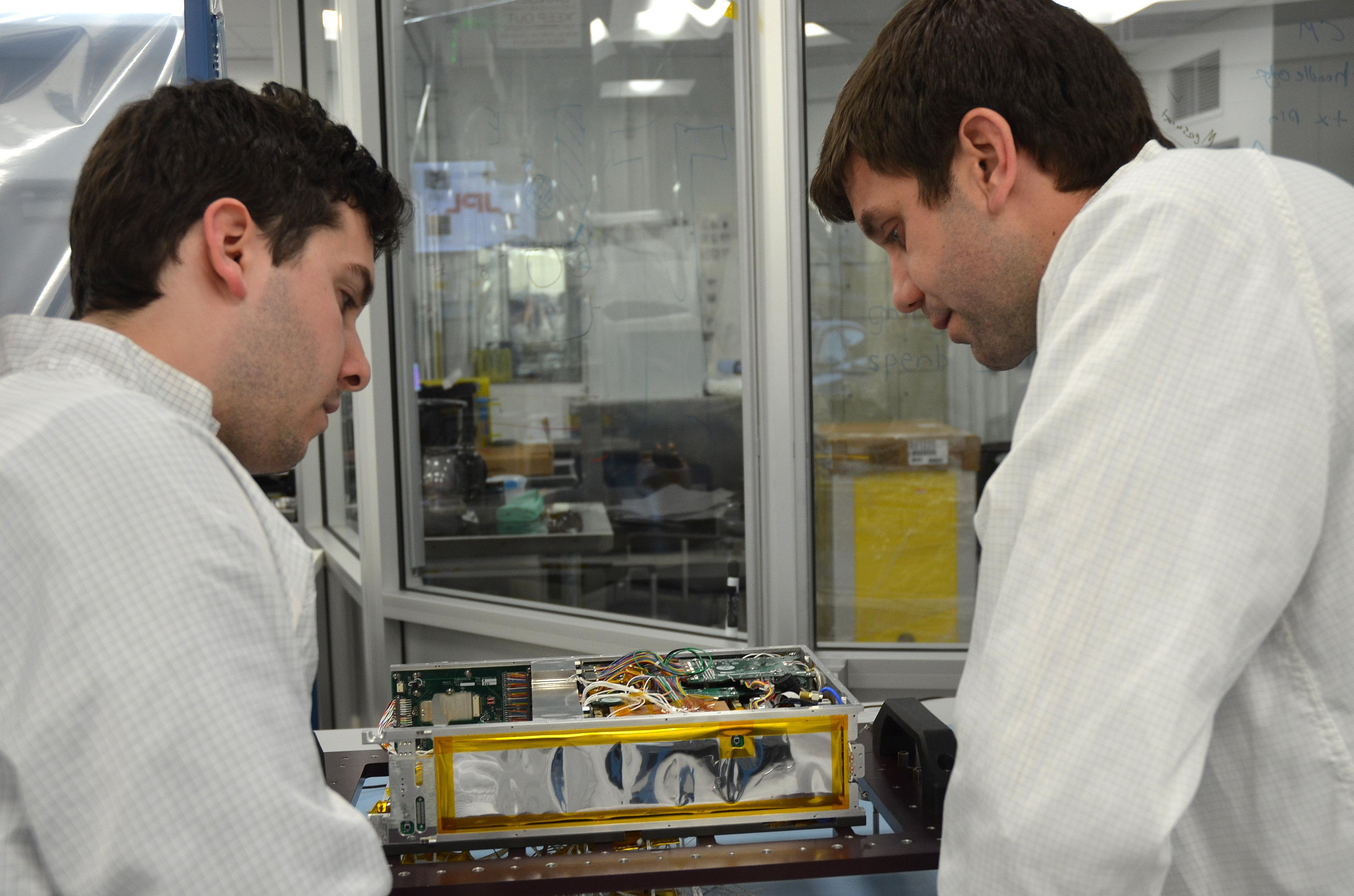 Engineers for NASA's MarCO (Mars Cube One) technology demonstration inspect one of the two MarCO CubeSats. Cody Colley, MarCO integration and test deputy, left, and Andy Klesh, MarCO chief engineer, are on the team at NASA's Jet Propulsion Laboratory, Pasadena, California, preparing twin MarCO CubeSats.