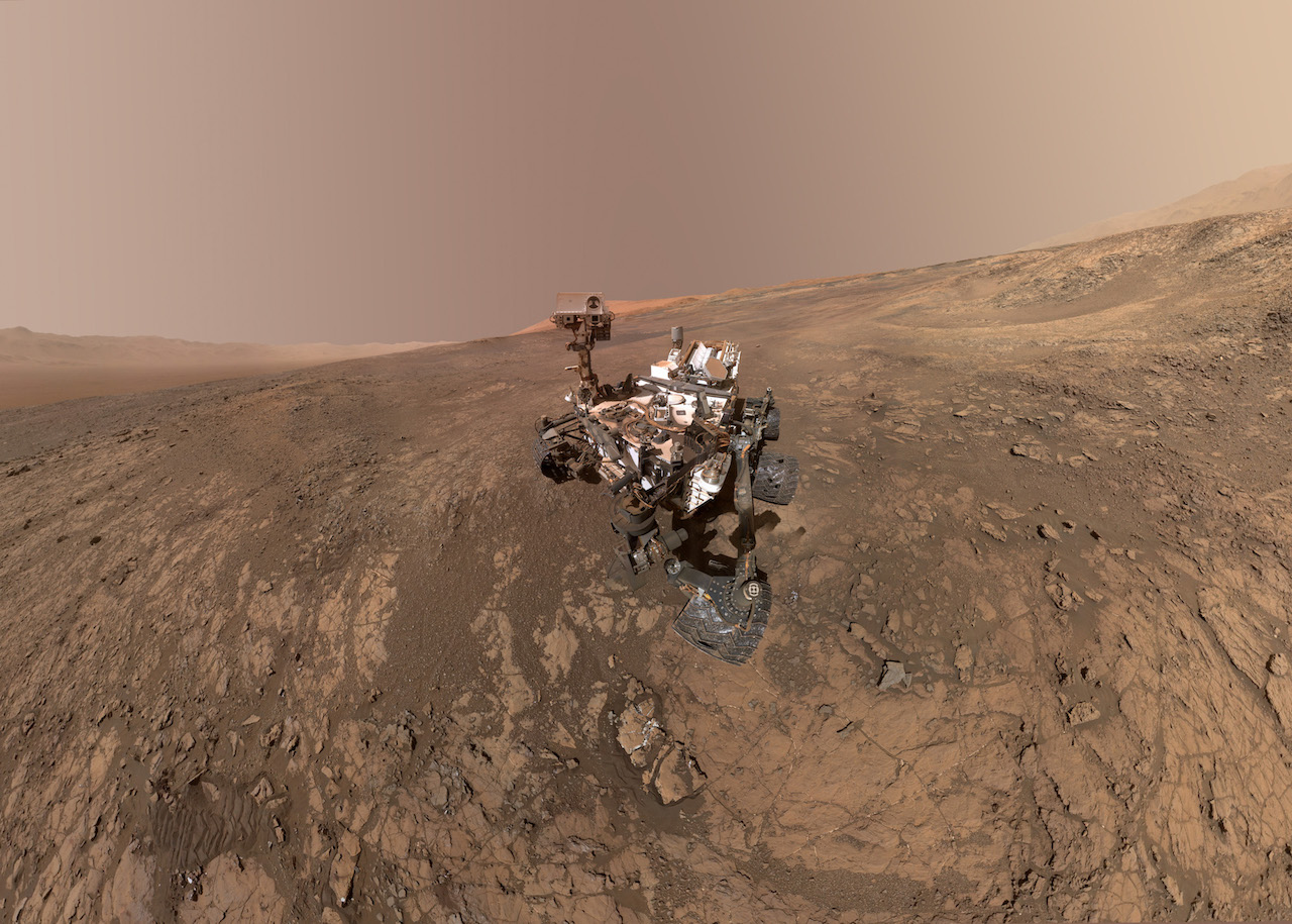 rover on mars surface with mountain in background