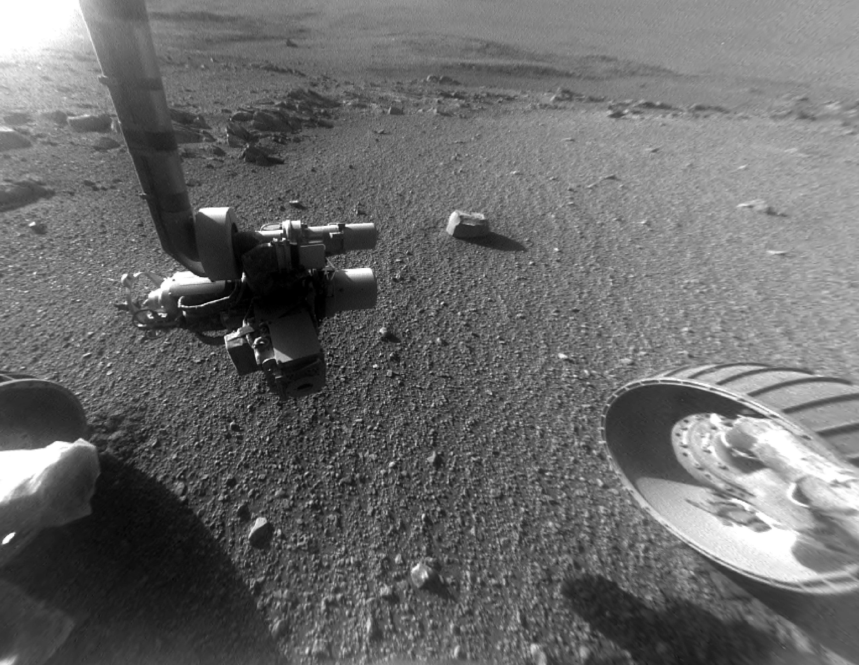 rover wheel and robot arm over rocky ground