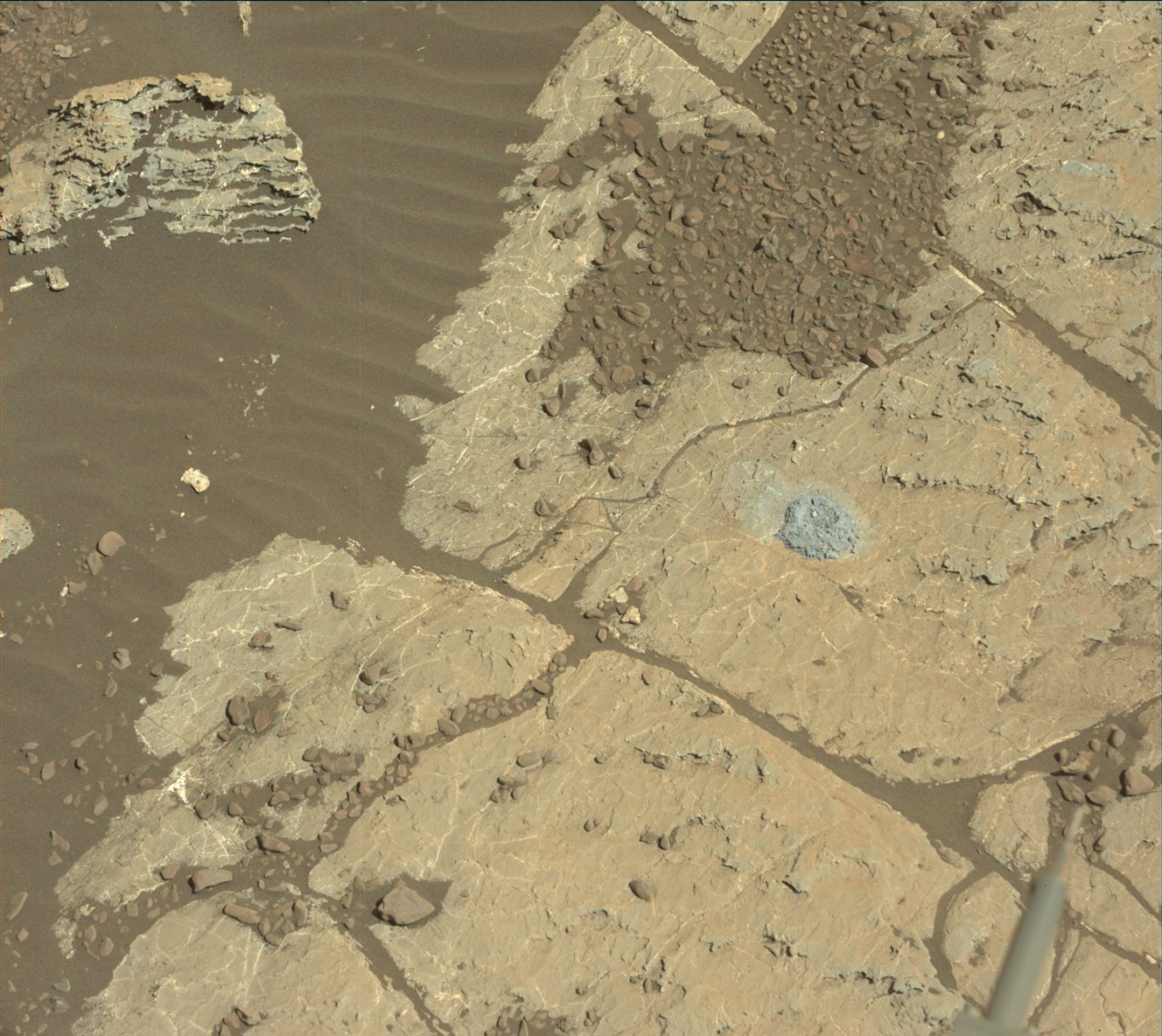 Rock surface with small drill hole and pile of drill tailings.