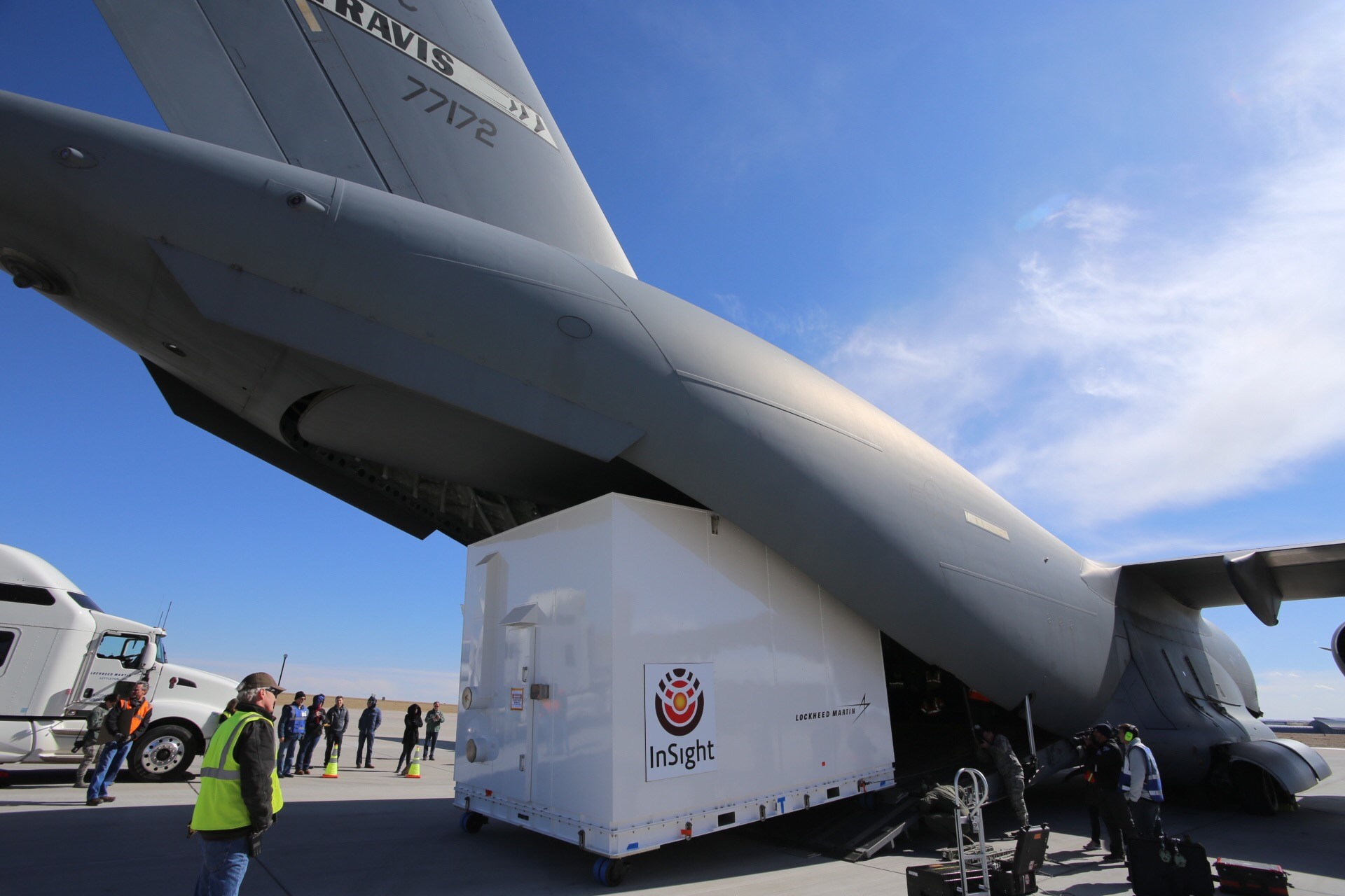 large crate being loaded into military transport plane