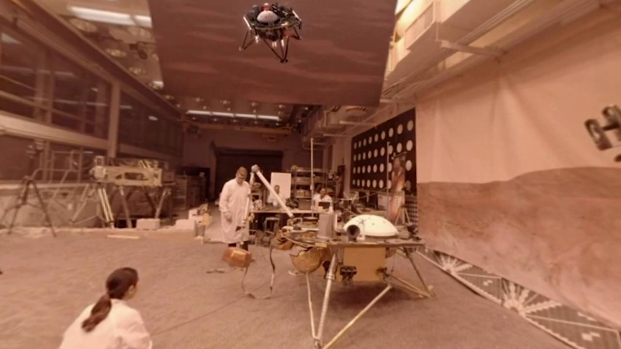engineers in lab with spacecraft