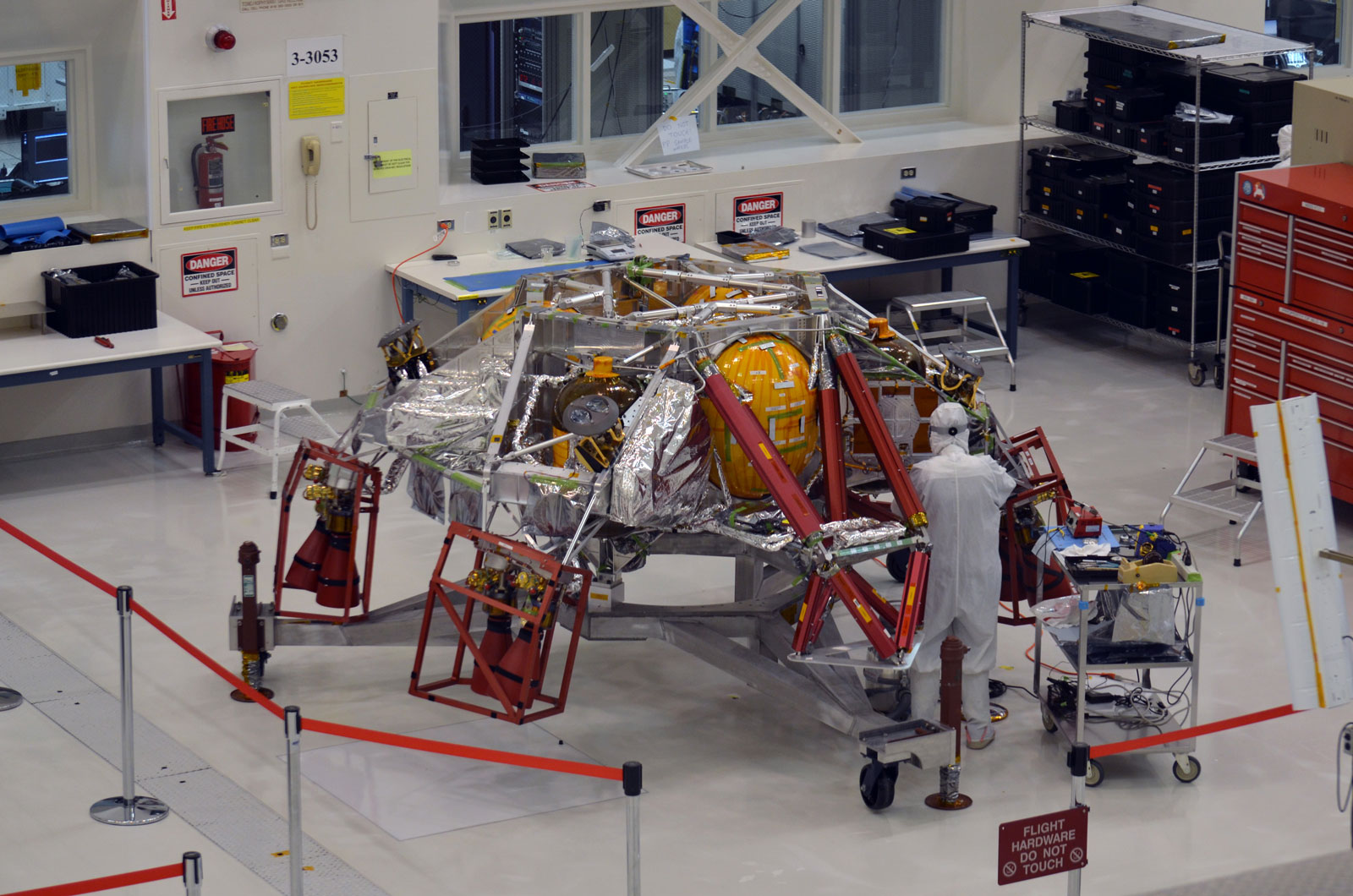A technician working on the descent stage for NASA's Mars 2020 mission inside JPL's Spacecraft Assembly Facility.