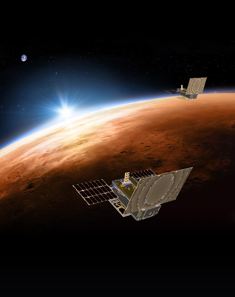 An artist's rendering of the twin Mars Cube One (MarCO) spacecraft flying over Mars with Earth in the distance.
