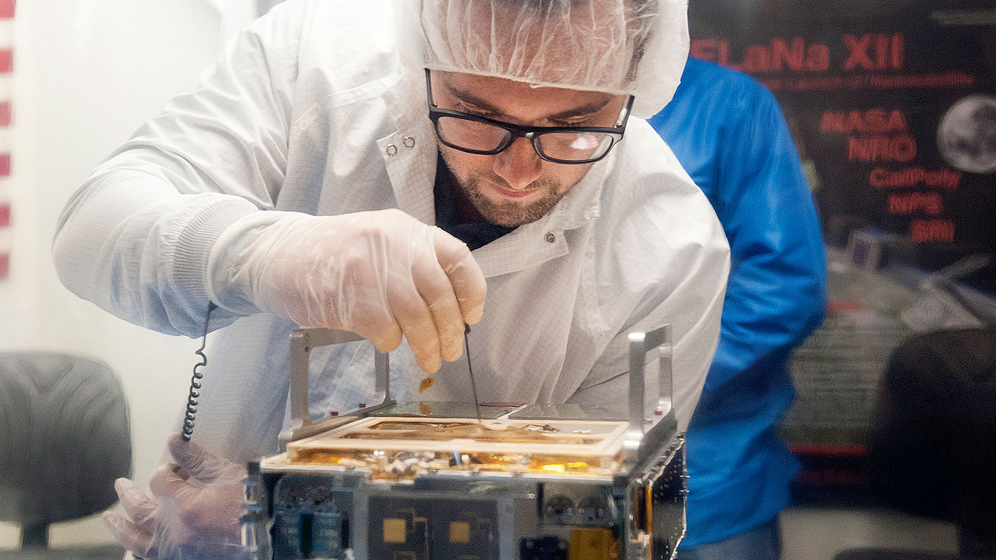 An engineer makes an adjustment on the CubeSat.