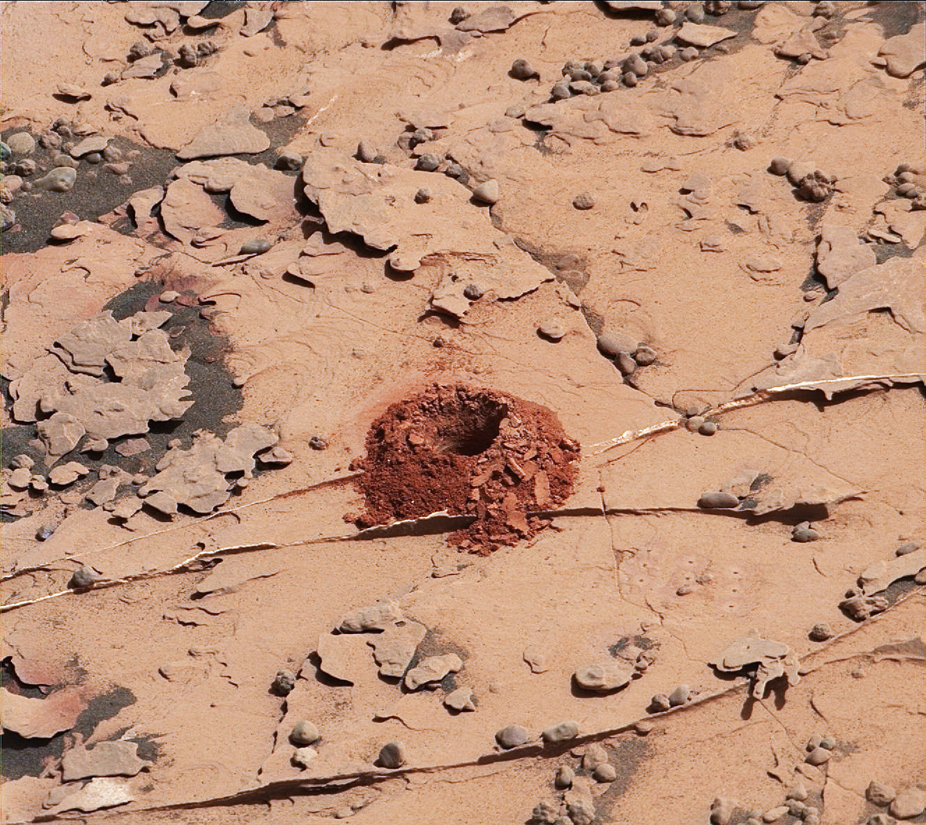 A close-up image of a 2-inch-deep hole produced using a new drilling technique for NASA's Curiosity rover.