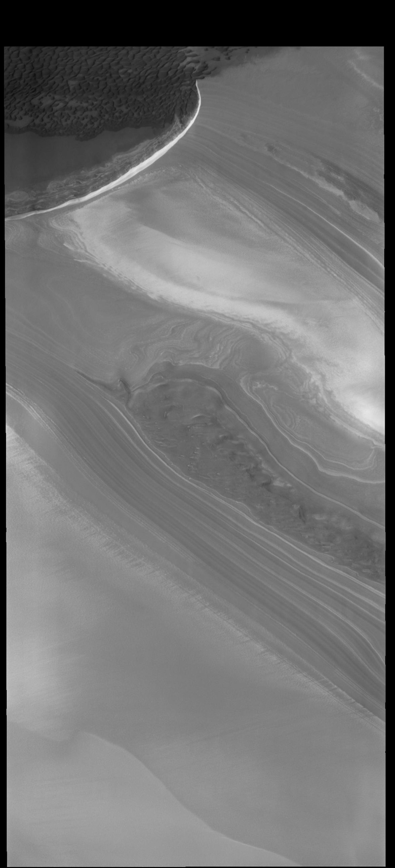 This image from NASA's 2001 Mars Odyssey spacecraft shows part of the margin of the north polar cap and the surrounding plains. The layering of the ice is easily visible due to the dust that is deposited on the top of the ice every year, creating layering over millions of years.