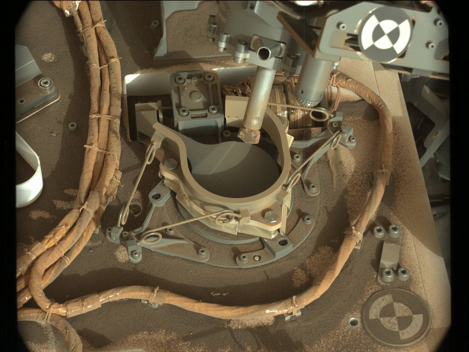 The drill bit of NASA's Curiosity Mars rover over one of the sample inlets on the rover's deck. The inlets lead to Curiosity's onboard laboratories. This image was taken on Sol 2068 by the rover's Mast Camera (Mastcam).