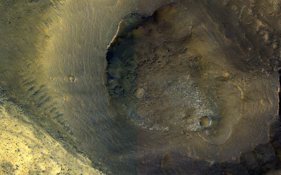 This image from NASA's Mars Reconnaissance Orbiter shows a hill with a central crater on the floor of Valles Marineris. It could be either a real volcano, the kind that erupts lava, or a sedimentary structure called a mud volcano.