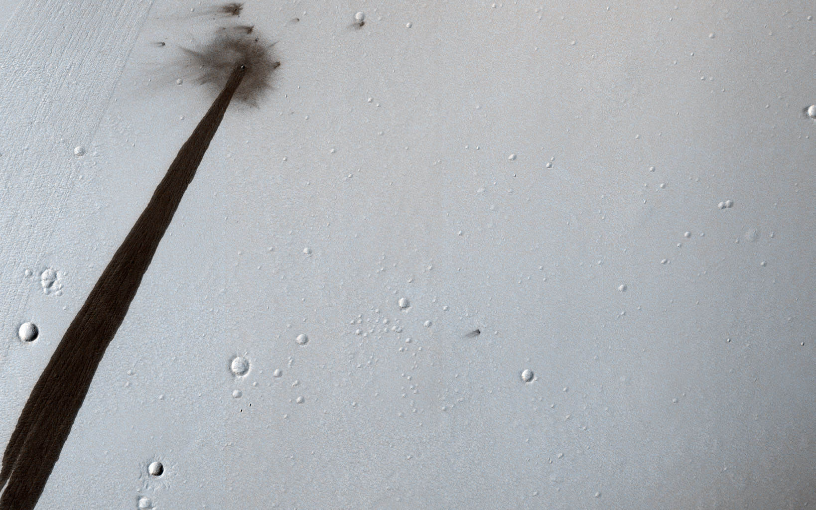 This image from NASA's Mars Reconnaissance Orbiter shows an impact crater that triggered a slope streak. When a meteoroid hit the surface and exploded to make the crater, it destabilized the slope and initiated this avalanche.