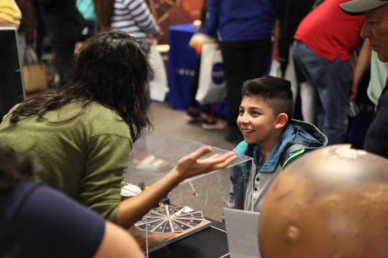 This image shows Amruta Mehta, a member of the Mars InSight Roadshow, speaking with a boy at one of the Roadshow's stops in Santa Maria in May 2018.