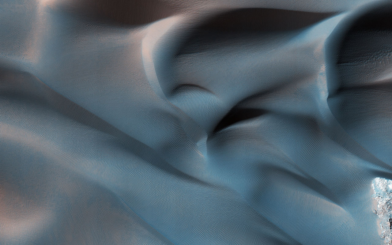 This image, acquired on January 2, 2014, by NASA's Mars Reconnaissance Orbiter, shows dune fields located among canyon wall slopes.