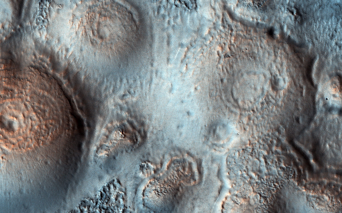 This image shows relatively bright mounds, hundreds of meters in size, scattered throughout darker and diverse surfaces in Chryse Planitia. The largest shows a central pit, similar to the collapsed craters in some Earth volcanoes.