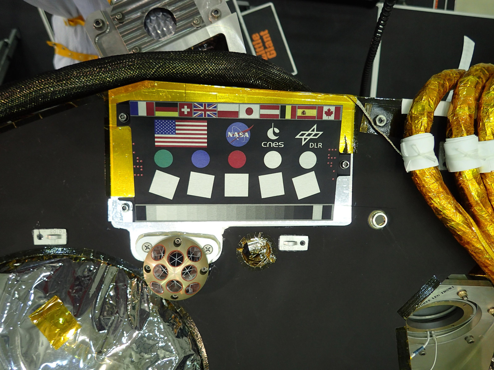 A camera calibration target sits on the deck of the NASA's InSight lander, adorned with the flags of the countries participating in the mission.