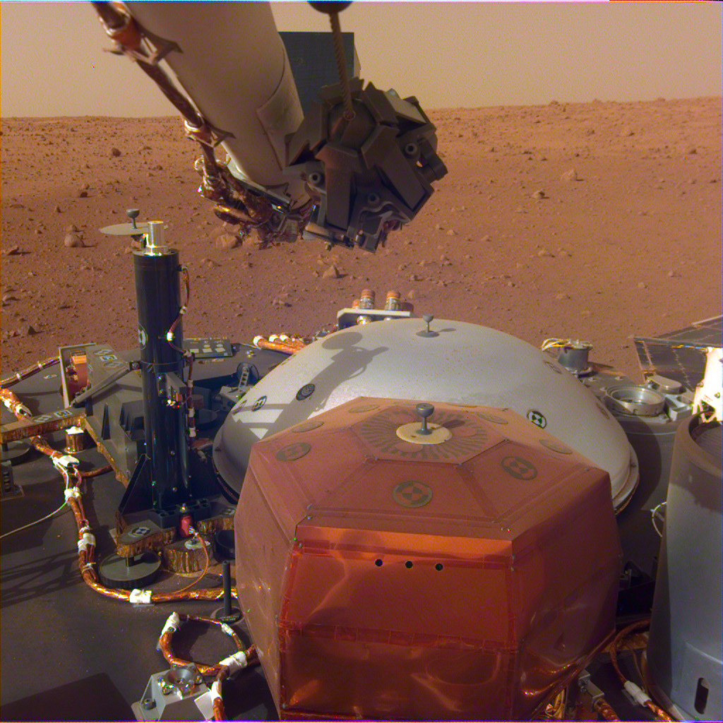 This image from InSight's robotic-arm mounted Instrument Deployment Camera shows the instruments on the spacecraft's deck, with the Martian surface of Elysium Planitia in the background. The image was received on Dec. 4, 2018 (Sol 8).