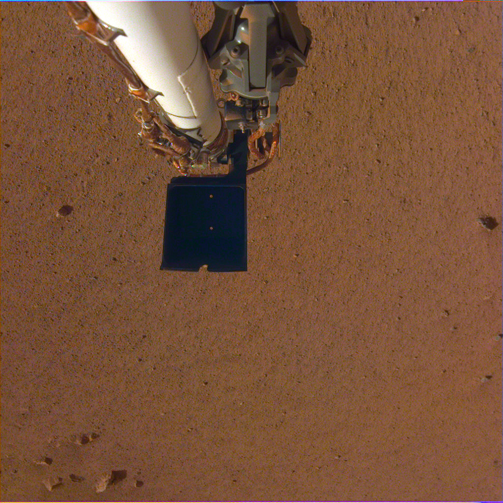 An image of InSight's robotic arm, with its scoop and stowed grapple, poised above the Martian soil. The image was received on Dec. 4, 2018 (Sol 8).