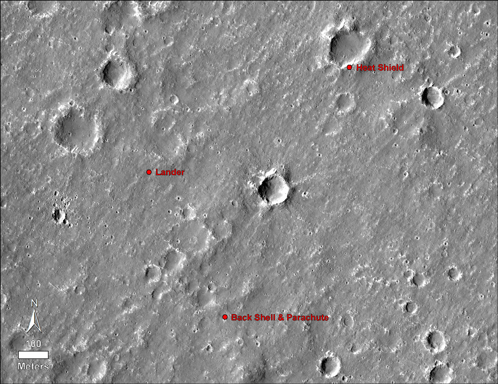 An annotated image of the surface of Mars, taken by the HiRISE camera on NASA's Mars Reconnaissance Orbiter (MRO) on May 30, 2014. The annotations — added after InSight landed on Nov. 26, 2018 — display the locations of NASA's InSight lander, its heat shield and parachute.