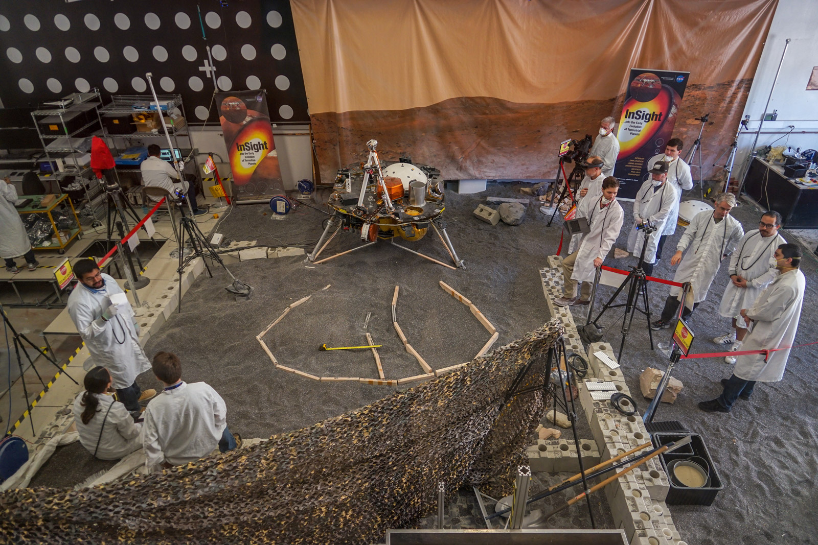 Engineers in Pasadena, California, sculpt a gravel-like material to mimic the terrain in front of NASA's InSight lander on Mars. Recreating the exact conditions will allow them to practice setting down the lander's instruments here on Earth before it's done on Mars.