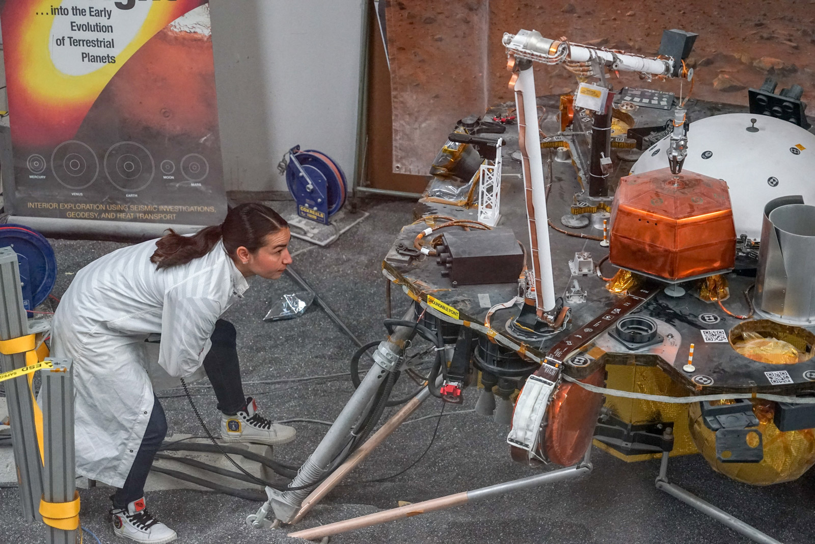 Engineer Marleen Sundgaard watches as the robotic arm on a test version of NASA's Mars InSight lander grasps a model of the spacecraft's seismometer. This work was done at NASA's Jet Propulsion Laboratory in Pasadena, California.