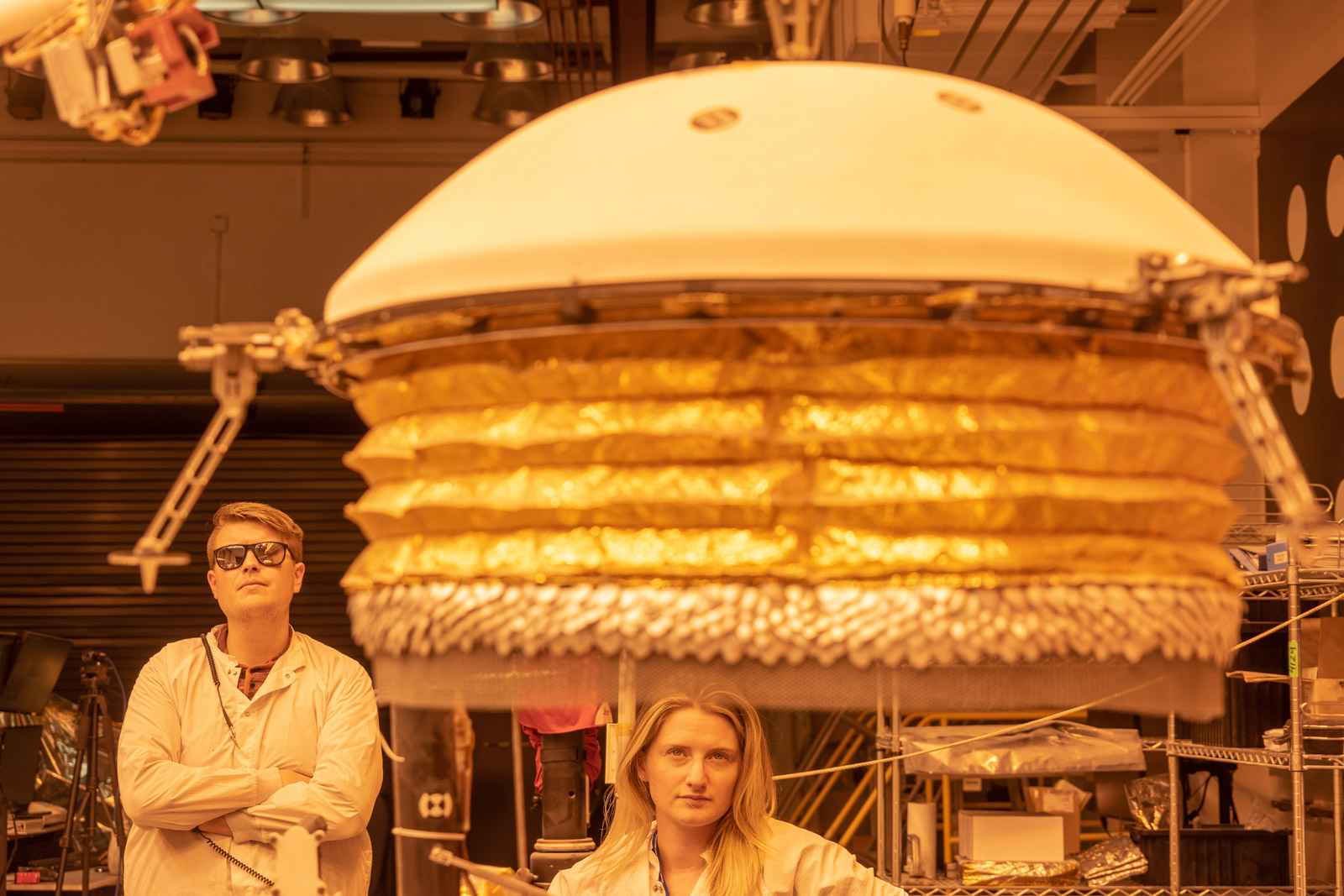 ForeSight, a fully functional, full-size model of NASA's InSight lander, practices deploying a model of the lander's Wind and Thermal Shield while engineers Phil Bailey (left) and Jaime Singer (center) look on. The Wind and Thermal Shield protects InSight's seismometer. This testing was done at NASA's Jet Propulsion Laboratory in Pasadena, California.