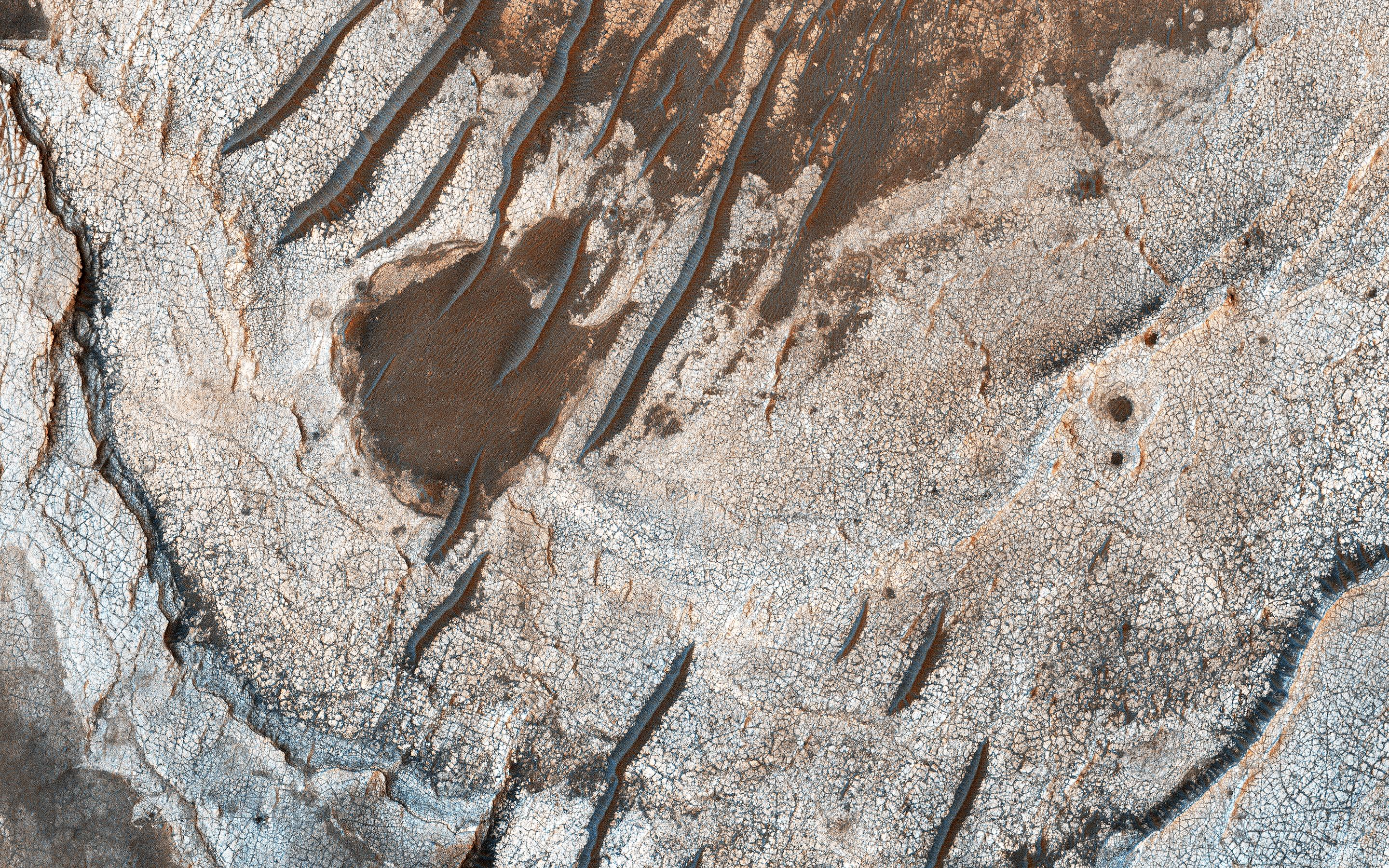 This image acquired on December 8, 2018 by NASAs Mars Reconnaissance Orbiter, shows erosion of the surface revealing several shades of light toned layers, likely sedimentary deposits.