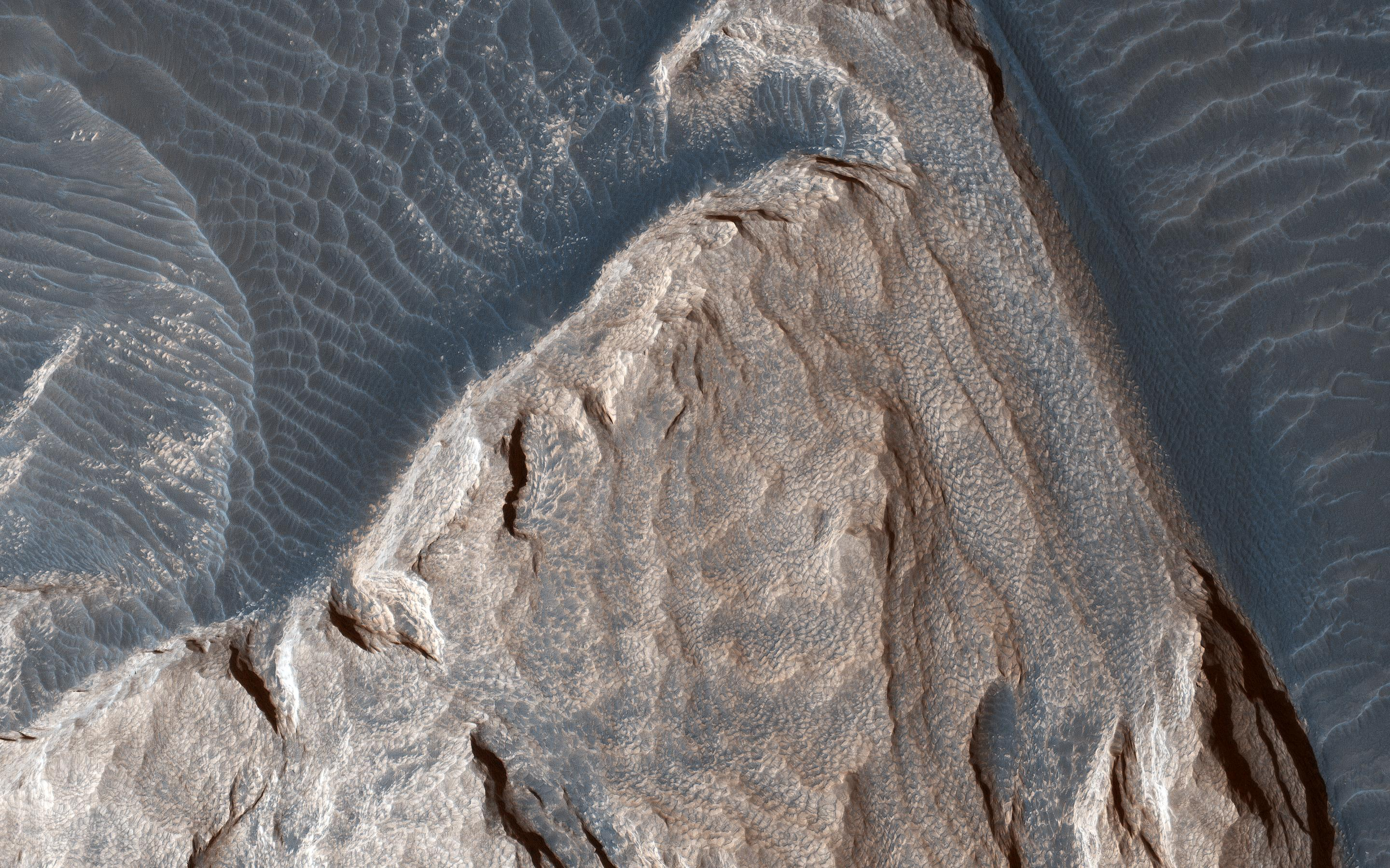 This image acquired on December 5, 2018 by NASAs Mars Reconnaissance Orbiter, shows ripples in the sand which tell us which way the wind was moving and how it was diverted around these rock formations.
