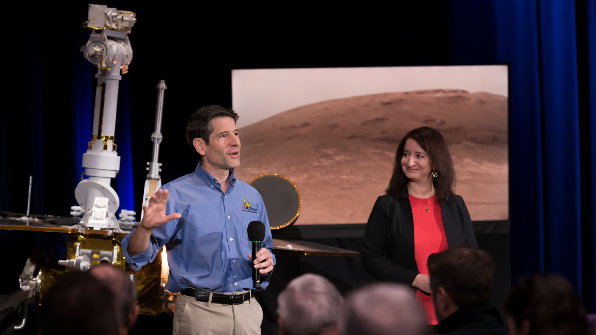 With a model of NASA's Opportunity rover behind him, John Callas, project manager of the Spirit and Opportunity Mars rovers, speaks about the rovers' achievements at the agency's Jet Propulsion Laboratory in Pasadena, California. Deputy Project Scientist Abigail Fraeman (right) looks on.