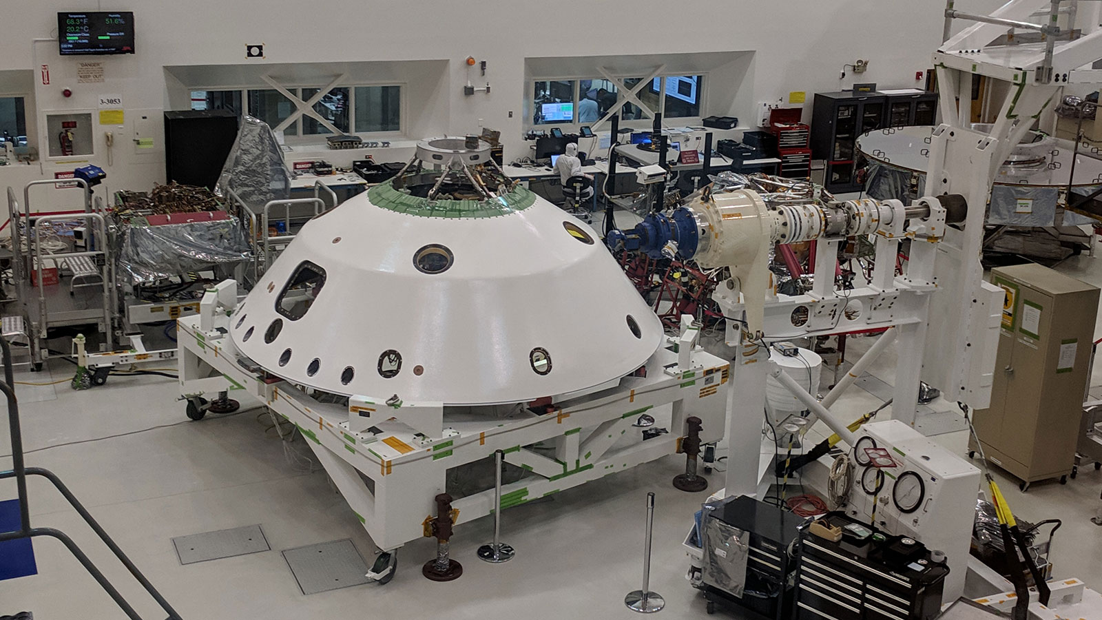 The backshell that will help protect the Mars 2020 rover during its descent into the Martian atmosphere visible in the foreground. A technician on the project monitors the progress of Systems Test 1.