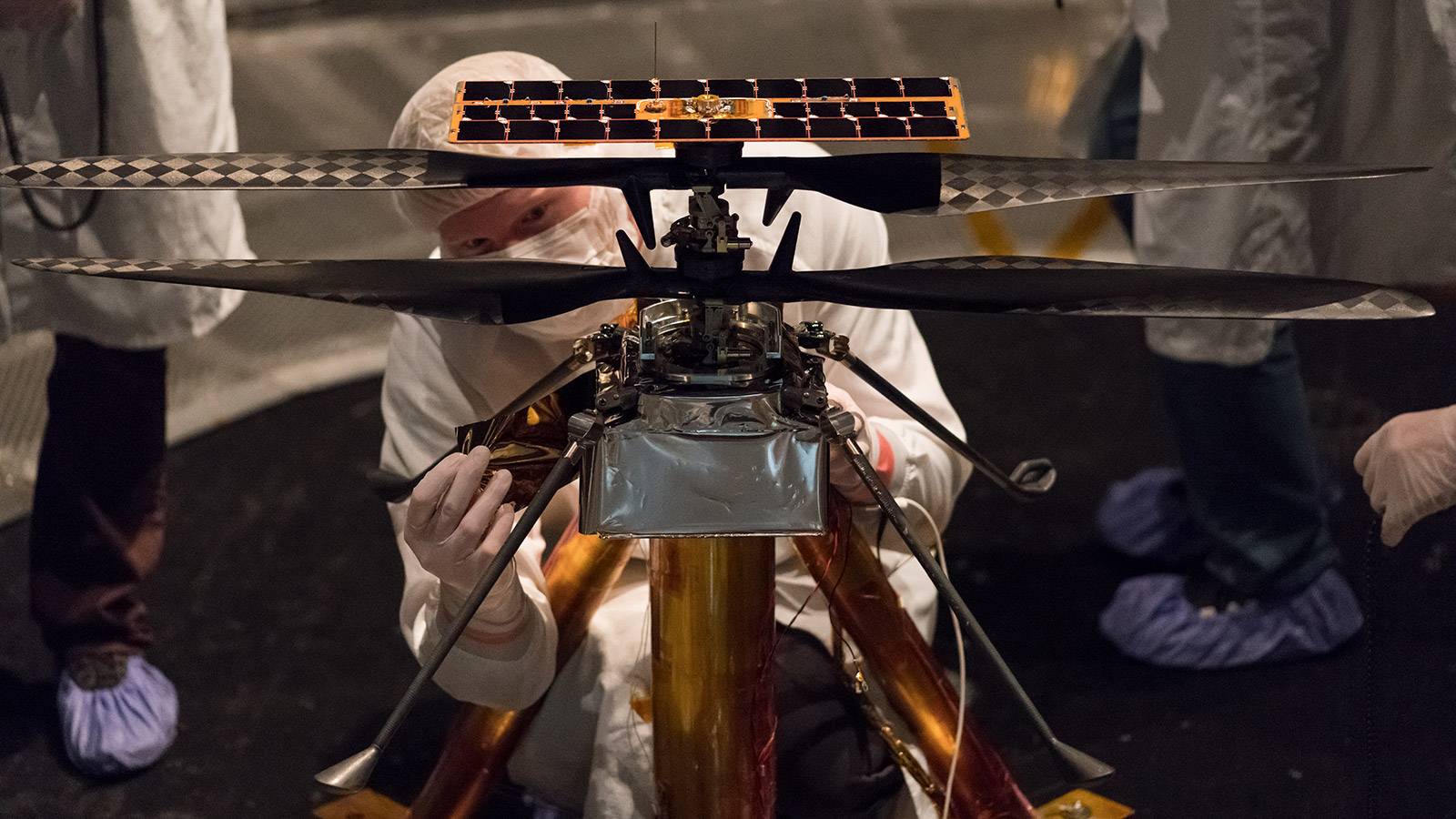 Members of the NASA Mars Helicopter team attach a thermal film to the exterior of the flight model of the Mars Helicopter.