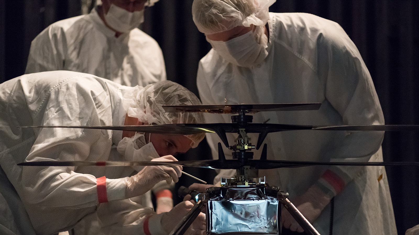 Members of NASA's Mars Helicopter team attach a thermal film enclosure to the fuselage of the flight model.
