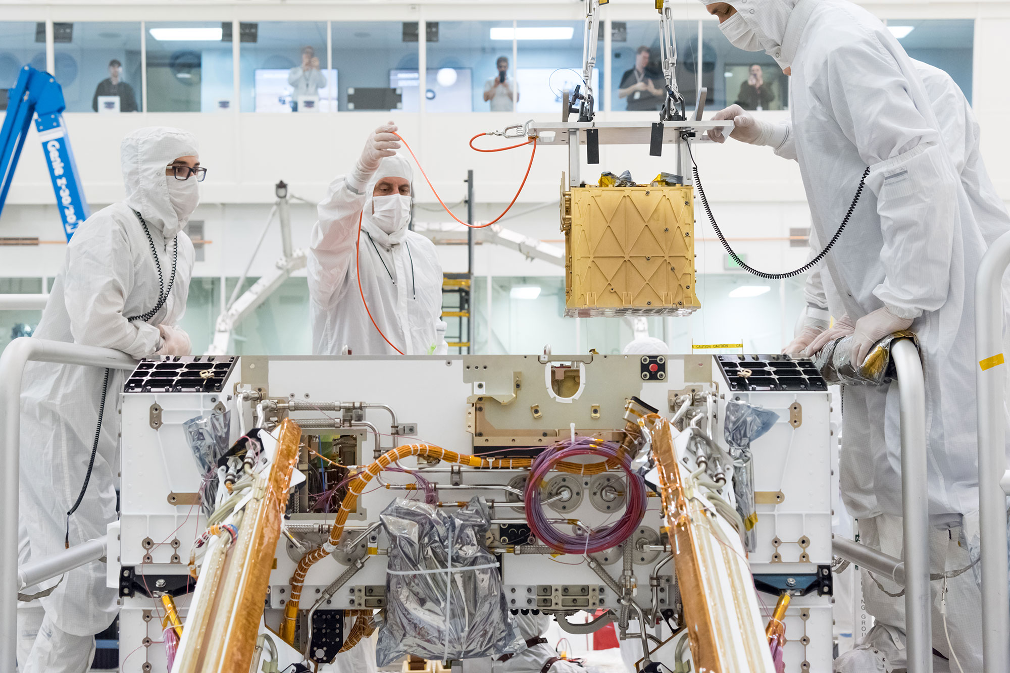 Engineers in white smocks lower a gold-colored cube into the rover