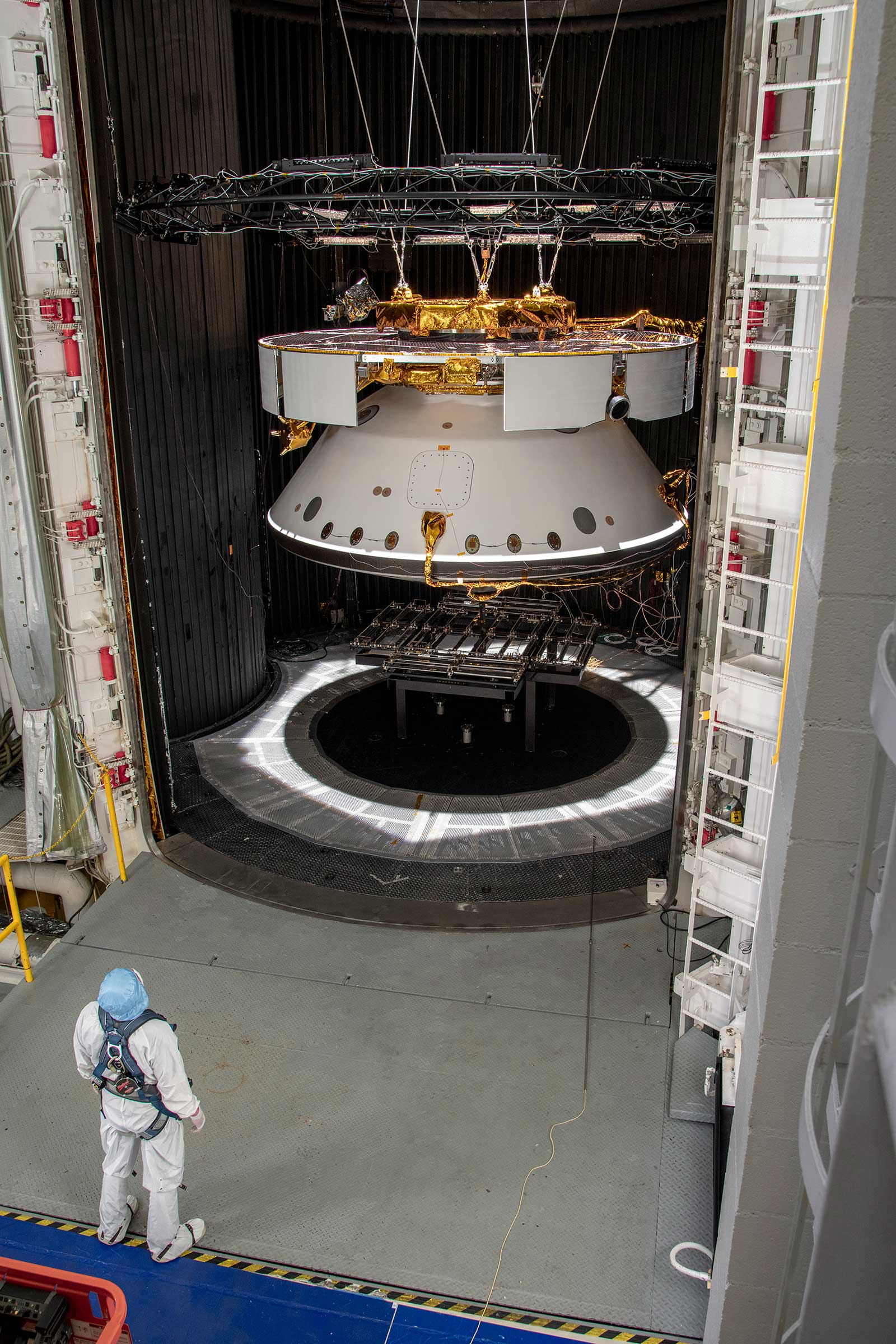 An engineer inspects the completed spacecraft that will carry NASA's next Mars rover to the Red Planet, prior to a test in the Space Simulator Facility at NASA's Jet Propulsion Laboratory in Pasadena, California.