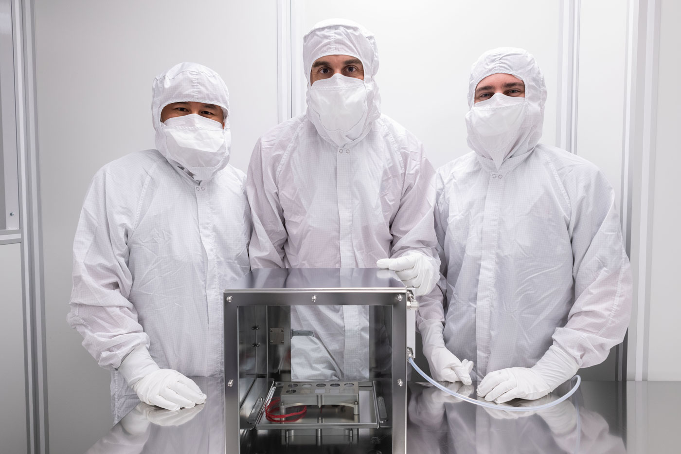 Image of engineers with the Mars 2020 SHERLOC Calibration Target in a clean room at NASA's Johnson Space Center.