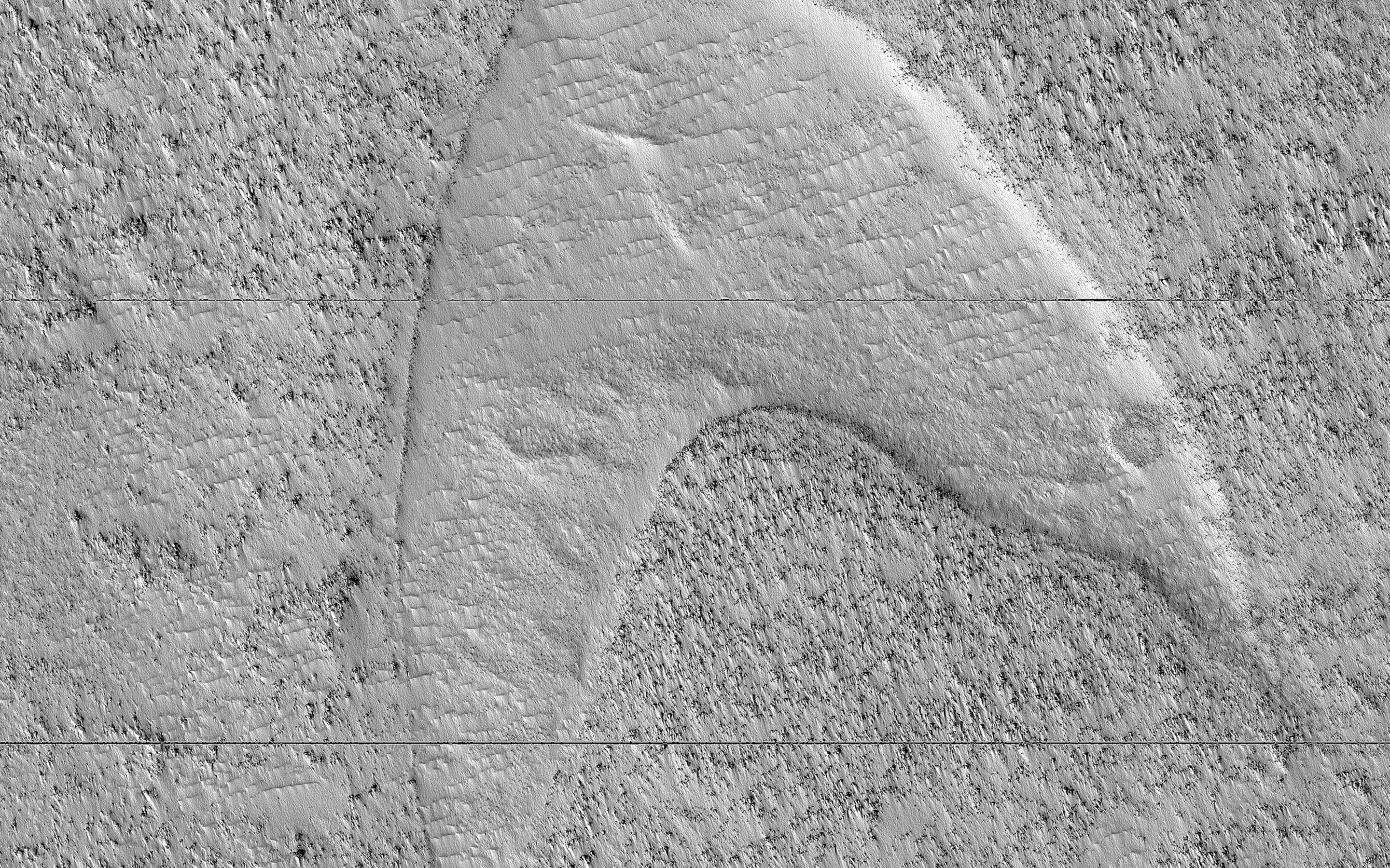 This image, acquired on April 22, 2019 by NASAs Mars Reconnaissance Orbiter, shows curious chevron shapes in southeast Hellas Planitia which are the result of a complex story of dunes, lava, and wind.