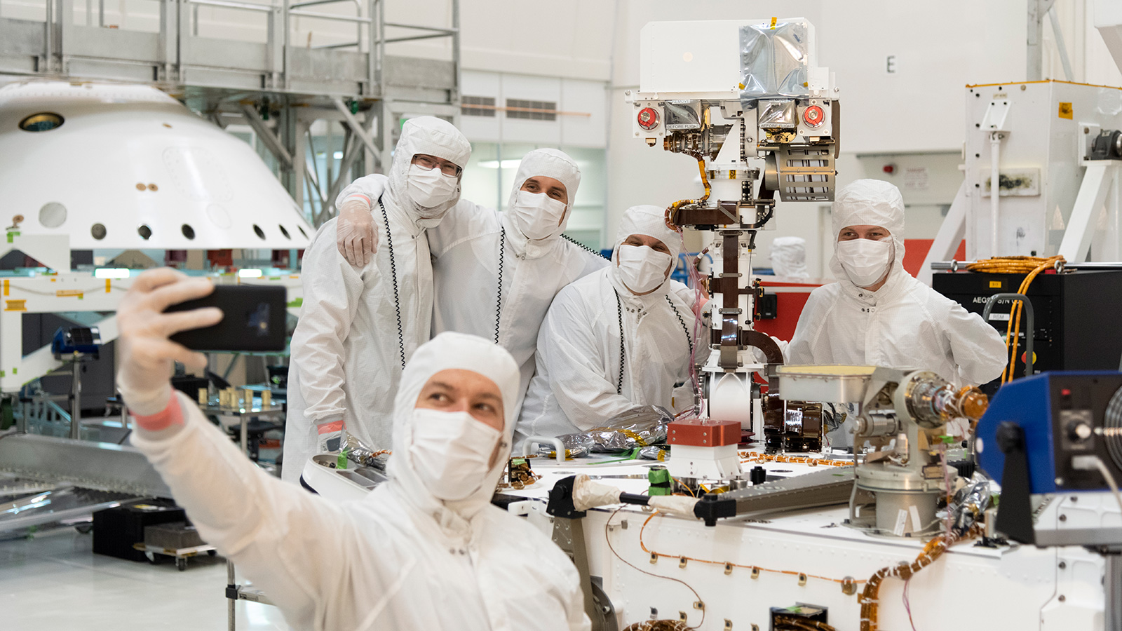 Members of NASA's Mars 2020 project take a moment after attaching the remote sensing mast to the Mars 2020 rover.