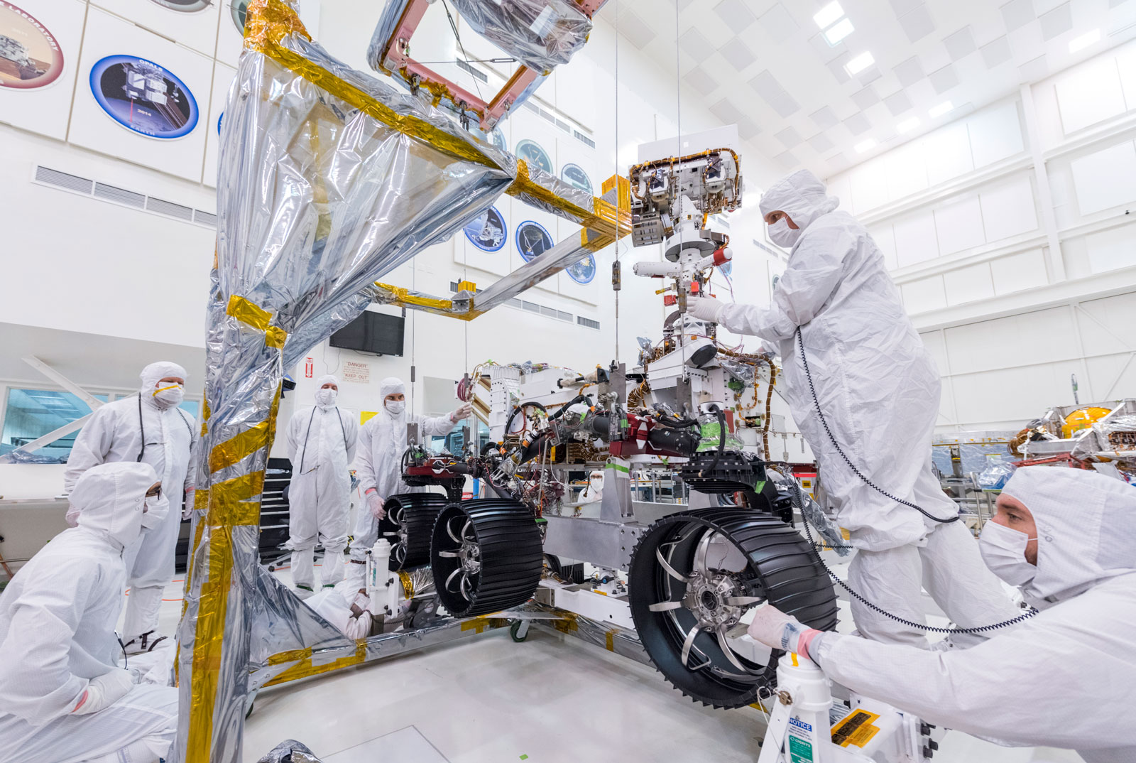 In this image, taken on June 13, 2019, engineers at JPL install the starboard legs and wheels — otherwise known as the mobility suspension — on the Mars 2020 rover.