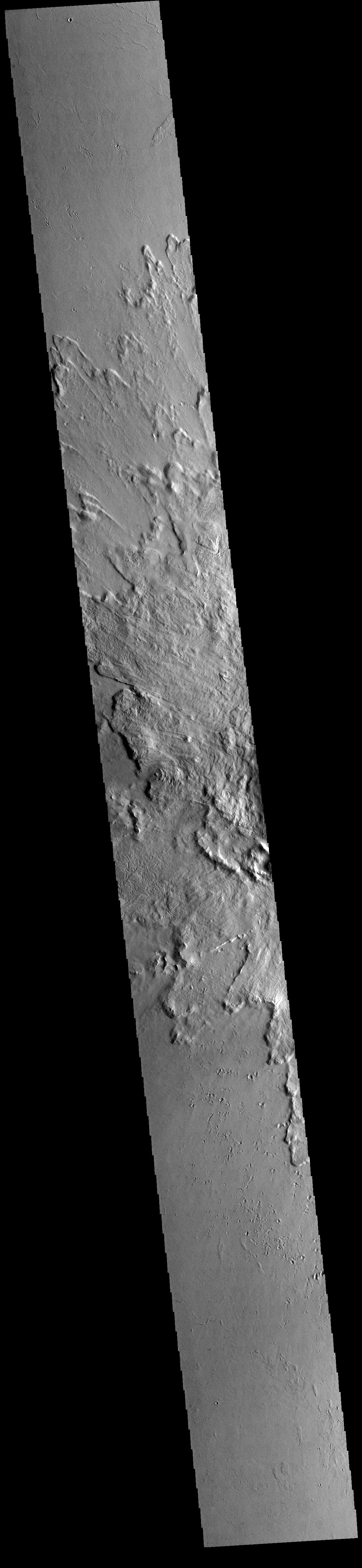 This image from NASAs Mars Odyssey shows part of the ejecta blanket of Tooting Crater. Tooting Crater is located west of Olympus Mons.