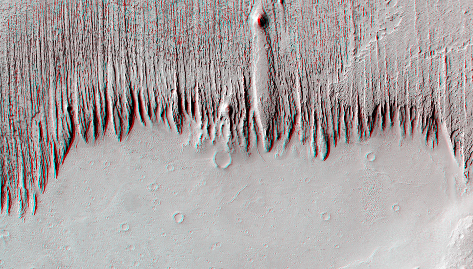 The material in the upper portion of this image, perhaps hardened volcanic ash deposits, is being eroded into parallel long, thin ridges called yardangs by the strong prevailing winds.
