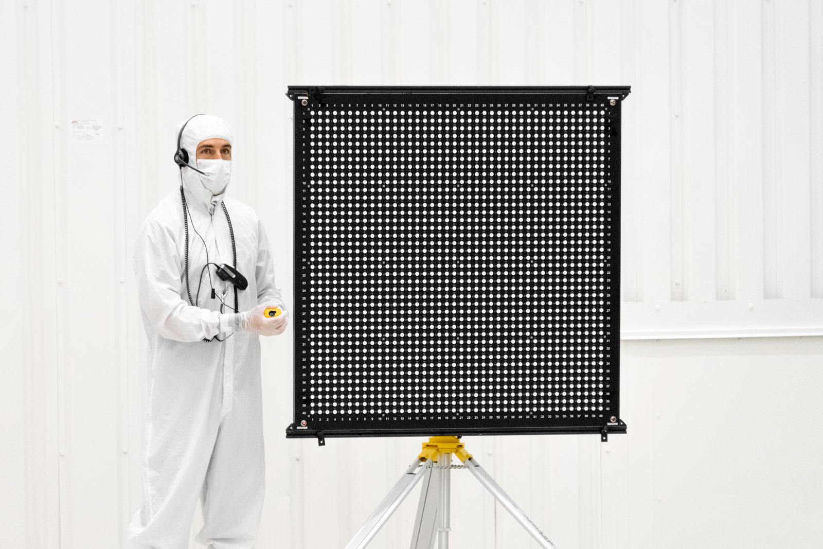 Engineer Chris Chatellier stands next to a target board with 1,600 dots. The board was one of several used on July 23, 2019, in the Spacecraft Assembly Facility's High Bay 1 at NASA's Jet Propulsion Laboratory in Pasadena, California, to calibrate the forward-facing cameras on the Mars 2020 rover.