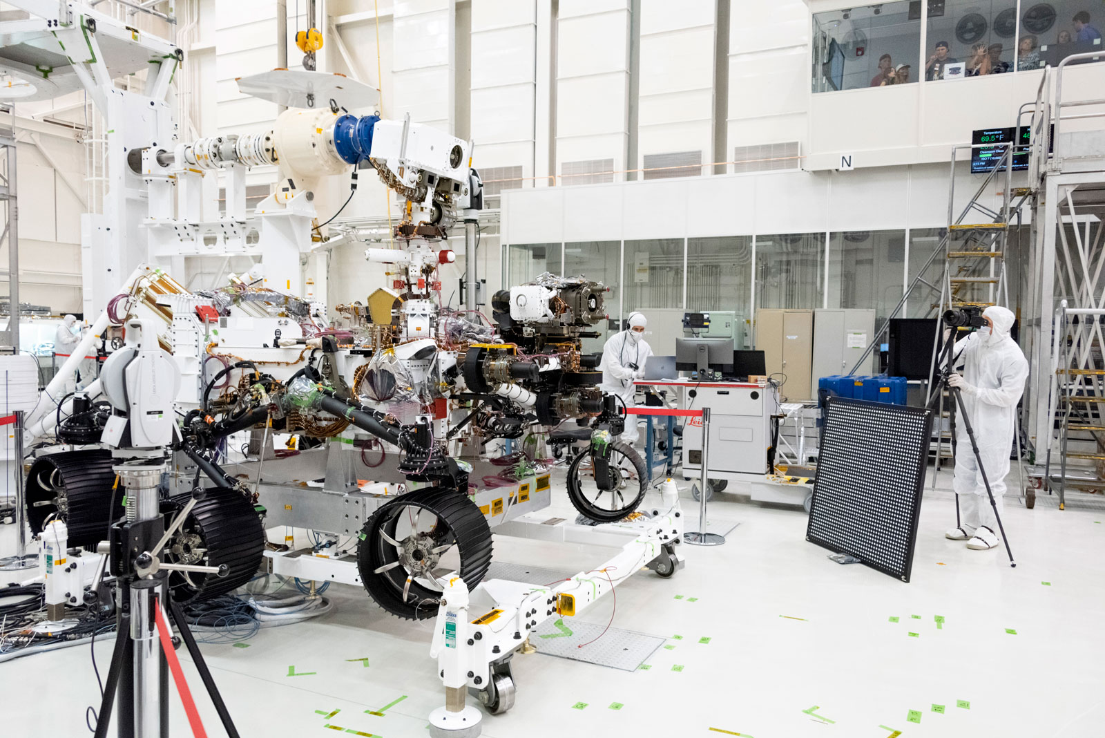 In this image, engineers test cameras on the top of the Mars 2020 rover's mast and front chassis.