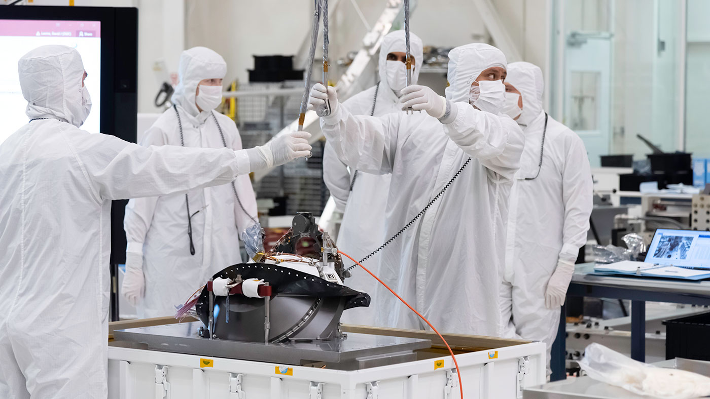 In this image, taken on Aug. 5, 2019, engineers at NASA's JPL  lift the Mars 2020 rover's bit carousel from its storage container. The bit carousel is at the heart of the rover's Sample Caching System.