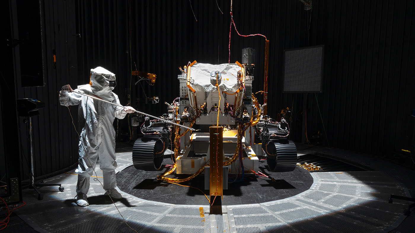 An engineer working on NASA's Mars 2020 mission uses a solar intensity probe to measure and compare the amount of artificial sunlight that reaches different portions of the rover.